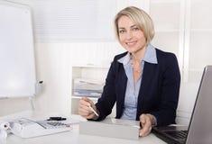 Atrakcyjna szczęśliwa stara lub starsza biznesowa kobieta w biurze. Zdjęcie Stock