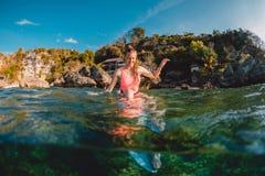 Atrakcyjna szczęśliwa surfingowiec dziewczyna z surfboard Surfingowiec siedzi przy deską w oceanie obrazy royalty free