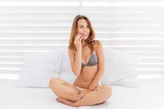 Atrakcyjna uśmiechnięta dziewczyna opowiada na telefonie w bikini obrazy stock