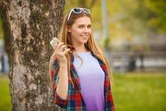 Atrakcyjna uśmiechnięta dziewczyna trzyma telefon komórkowego w lata miasta parku Nowożytna szczęśliwa kobieta z smartphone, plen Zdjęcia Stock