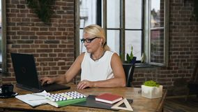 Atrakcyjna w średnim wieku caucasian kobieta jest ubranym szkła siedzi przy stołem z laptopem podczas dnia roboczego w eleganckim zbiory