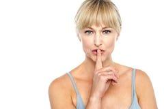 Atrakcyjna w średnim wieku kobieta gestykuluje ciszę Zdjęcie Royalty Free