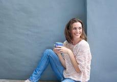 Atrakcyjna w połowie dorosła kobieta relaksuje z filiżanką kawy fotografia stock