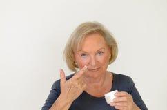 Atrakcyjna w średnim wieku kobieta stosuje creme Fotografia Royalty Free