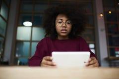 Atrakcyjna zadumana modniś dziewczyna ogląda webinar używa 4G internet w kawiarni w szkłach Zdjęcie Stock