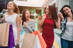 Atrakcyjne i zadowolone dziewczyny chodzą w centrum handlowym wpólnie Trzymają torby z materiałem Dziewczyny są roześmiane i obrazy royalty free