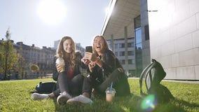 Atrakcyjne nastoletnie dziewczyny śmia się przy zabawa obrazkami przez interneta siedzi outdoors w parku z smartphone zbiory