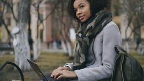 Atrakcyjnego amerykanina afrykańskiego pochodzenia studencka dziewczyna pisać na maszynie na laptopu obsiadaniu na ławce blisko u zbiory