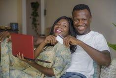 Atrakcyjnego czarnego afrykanina pary kanapy leżanki Amerykański networking z laptop bankowość online, interneta zakupy w domu lu obrazy royalty free
