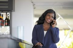 Atrakcyjnego i szczęśliwego czarnego afrykanina amerykańska kobieta pracuje od restauraci prętowy opowiadać na telefonie komórkow Zdjęcie Stock