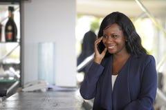 Atrakcyjnego i szczęśliwego czarnego afrykanina amerykańska kobieta pracuje od restauraci prętowy opowiadać na telefonie komórkow Zdjęcie Royalty Free
