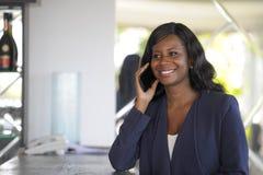 Atrakcyjnego i szczęśliwego czarnego afrykanina amerykańska kobieta pracuje od restauraci prętowy opowiadać na telefonie komórkow Obrazy Royalty Free