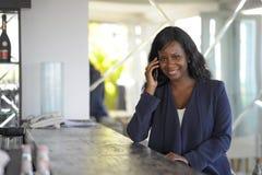 Atrakcyjnego i szczęśliwego czarnego afrykanina amerykańska kobieta pracuje od restauraci prętowy opowiadać na telefonie komórkow Zdjęcia Royalty Free