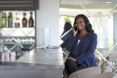 Atrakcyjnego i szczęśliwego czarnego afrykanina amerykańska kobieta pracuje od restauraci prętowy opowiadać na telefonie komórkow Obrazy Stock