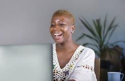Atrakcyjnego i szczęśliwego modnisia afro Amerykańska kobieta pracuje na laptopu ono uśmiecha się satysfakcjonuję cieszący się in Obraz Stock
