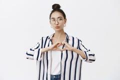 Atrakcyjnego kobiecego mody blogger kształtujący serce z oddaje klatkę piersiową, składający wargi w buziaku, dawać mwah, bierze fotografia royalty free