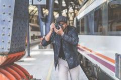 Atrakcyjnego mężczyzna turystyczny fotograf robi fotografii na analogowej rocznika modnisia filmu kamerze na dworcu Pojęcie podró Zdjęcia Stock