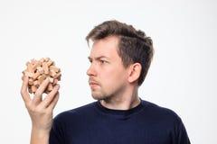 Atrakcyjnego 25 roczniaka biznesowy mężczyzna patrzeje wprawiać w zakłopotanie przy drewnianą łamigłówką Obraz Royalty Free