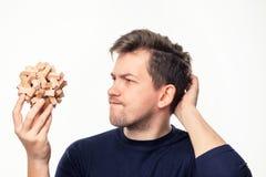 Atrakcyjnego 25 roczniaka biznesowy mężczyzna patrzeje wprawiać w zakłopotanie przy drewnianą łamigłówką Fotografia Royalty Free