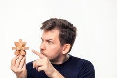 Atrakcyjnego 25 roczniaka biznesowy mężczyzna patrzeje wprawiać w zakłopotanie przy drewnianą łamigłówką Zdjęcie Royalty Free