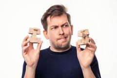 Atrakcyjnego 25 roczniaka biznesowy mężczyzna patrzeje wprawiać w zakłopotanie przy drewnianą łamigłówką Zdjęcia Stock