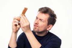 Atrakcyjnego 25 roczniaka biznesowy mężczyzna patrzeje wprawiać w zakłopotanie przy drewnianą łamigłówką Fotografia Stock