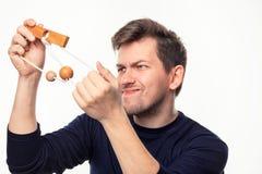Atrakcyjnego 25 roczniaka biznesowy mężczyzna patrzeje wprawiać w zakłopotanie przy drewnianą łamigłówką Obrazy Royalty Free