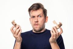 Atrakcyjnego 25 roczniaka biznesowy mężczyzna patrzeje wprawiać w zakłopotanie z drewnianą łamigłówką Fotografia Royalty Free