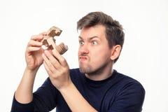 Atrakcyjnego 25 roczniaka biznesowy mężczyzna patrzeje wprawiać w zakłopotanie z drewnianą łamigłówką Zdjęcie Royalty Free