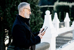 Atrakcyjnego z włosami architekta texting wiadomość na jego telefonie komórkowym podczas gdy wydający czas w miasto parku przy sł Fotografia Royalty Free