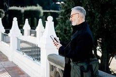 Atrakcyjnego z włosami biznesmena texting wiadomość na telefonie komórkowym podczas gdy wydający czas w miasto parku przy słonecz Fotografia Royalty Free