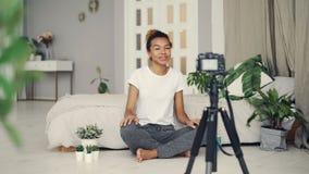 Atrakcyjnej amerykanin afrykańskiego pochodzenia dziewczyny kreatywnie blogger siedzi na podłoga jej mieszkanie jest magnetofonow zbiory