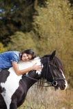 Atrakcyjnej brunetki żeński jeździec obejmuje jej hor Zdjęcia Stock
