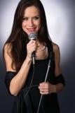 Atrakcyjnej brunetki wokalisty karaoke piosenkarza Żeński Muzykalny audio Fotografia Royalty Free