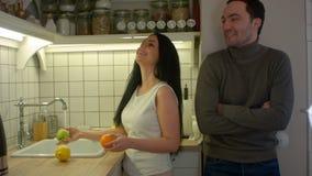 Atrakcyjnej kobiety płuczkowe owoc i opowiadać z przystojnym mężczyzna w kuchni zbiory