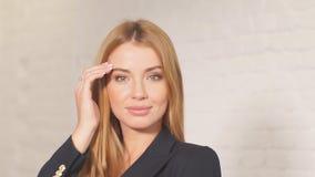 Atrakcyjnej młodej blondynki żeński loyer ubierał w formalnej odzieży ono uśmiecha się przy kamerą zbiory