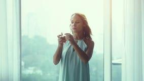 Atrakcyjnej młodej dziewczyny opatrunkowa toga rozpyla pachnidło woń na pnoramic nadokiennym tle z miasto widokiem podczas zbiory wideo