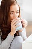 Atrakcyjnej młodej kobiety target791_0_ kawa w domu Obraz Royalty Free