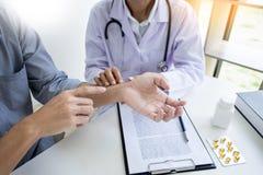 Atrakcyjnej samiec doktorski Egzamininuje dyskutować donosi z masażu cierpliwym cierpieniem od bólu pleców w klinice obraz stock