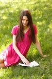 Atrakcyjnej szczęśliwej uśmiechniętej studenckiej nastoletniej dziewczyny czytelnicza książka plenerowa Zdjęcia Stock