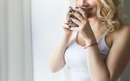 Atrakcyjni blondynki kobiety stojaki blisko okno z herbat? lub fili?anka kawy zdjęcie royalty free