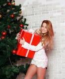 Atrakcyjni caucasian kobieta blondyny z czerwonym prezentem blisko bożych narodzeń Fotografia Royalty Free