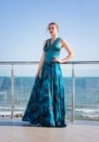 Atrakcyjni i seksowni potomstwa modelują w długiej sukni pozują na błękitnym dennym tle Powabna kobieta pozuje blisko morza Obrazy Stock
