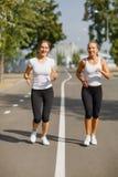 Atrakcyjni i uśmiechnięci dziewczyna biegacze na parkowym tle Ranku jogging Działający pojęcie obrazy royalty free