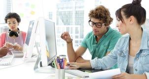 Atrakcyjni kreatywnie projektanci opowiada each inny podczas gdy pracujący zbiory wideo