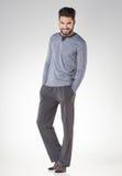 Atrakcyjni mężczyzna w pyjamas ono uśmiecha się odizolowywam na popielatym fotografia royalty free