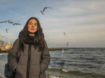 Atrakcyjni młoda dziewczyna stojaki na seashore i niebie denni †‹â€ ‹frajery wznoszą się w niebie zdjęcie stock