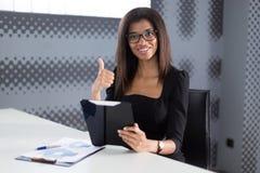 Atrakcyjni młodzi businesslady w czarnym silnym apartamencie siedzą przy biurowym stołem Obrazy Stock