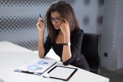 Atrakcyjni młodzi businesslady w czarnym silnym apartamencie siedzą przy biurowym stołem Fotografia Royalty Free