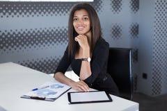 Atrakcyjni młodzi businesslady w czarnym silnym apartamencie siedzą przy biurowym stołem Zdjęcie Stock